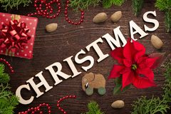 Christmas decoration and the word `christmas` on wooden background. Christmas decoration and the word `christmas` on rustic wooden background Royalty Free Stock Images