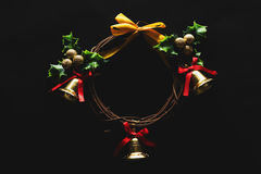 Christmas decoration, Wreath woven from the branch of the vine with golden bells and green leaf, on black background, low key imag Royalty Free Stock Photos