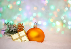 Christmas decoration. yellow ball and golden Gift box on snow Stock Photos