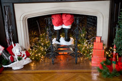 Christmas Decorations. Santa's pants and boots coming down the chimney with Christmas decorations around Stock Photos