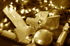 Christmas Decorations. Baubles, ribbons and crackers, with fairy light background.  Golden tone Royalty Free Stock Image
