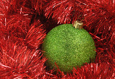 Christmas decorations. Christmas holiday decor with green sphere and red tinsel Royalty Free Stock Images