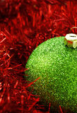 Christmas decorations. Christmas holiday decor with green sphere and red tinsel Royalty Free Stock Photography