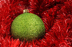 Christmas decorations. Cristmas holiday decor with green sphere and red tinsel Royalty Free Stock Images