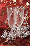 Christmas decorations. Two champagne glasses with silver bells on red christmas background Royalty Free Stock Image