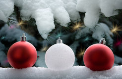 Christmas decorations. Row of three Christmas bauble decorations with snow covered fir tree in background with shining fairy lights Stock Photos
