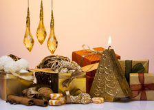 Christmas decorations. Gift boxes, candle, nuts and candy in a setting Stock Photos