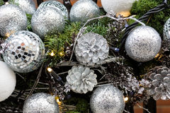 Christmas decorations. Close up of white shiny Christmas balls, lights and pinecones Stock Photos