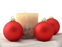 Christmas decorations. Red Christmas bubbles and a candle royalty free stock photography