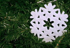 Christmas Decorations. Close-up of a pale blue snowflake on a background of artificial pine foliage Royalty Free Stock Images