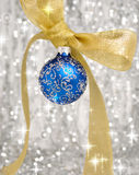 Christmas decorations. Blue christmas ball and ribbon over blurry background Royalty Free Stock Photo