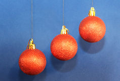 Christmas decorations. With red balls hanging on blue background Royalty Free Stock Photos