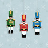 Christmas decorations. Blue snowflake background with hanging christmas nutcracker soldier ornaments Royalty Free Stock Photos