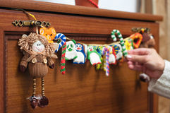 Christmas decorations. Like rag doll and homemade garland with different toys – penguin, panda, candy cane and other – hanging on brown wooden chest of Stock Photos