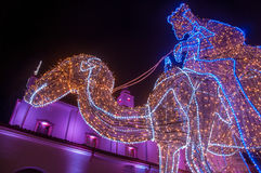 Christmas Decorations. A lit up camel with a church behind it Stock Photos