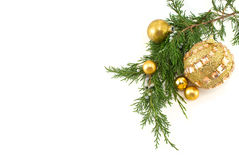 Christmas Decorations. Golden Christmas ball ornaments arranged with a juniper branch on a white background Stock Photos