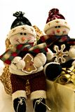 Christmas Decorations. Two stuffed smiling snowmen Christmas figures dressed in winter outerwear and hats.  One is sitting on a gold wrapped gift with a gold Royalty Free Stock Photos