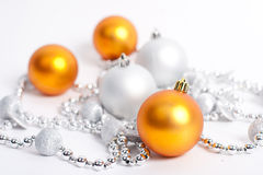 Christmas Decorations. Yellow balls and silver beads on a white Stock Photo