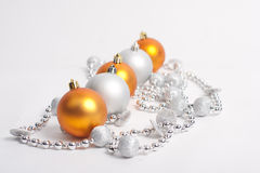 Christmas Decorations. Yellow balls and silver beads on a white Stock Image