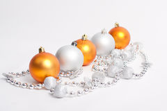 Christmas Decorations. Yellow balls and silver beads on a white Royalty Free Stock Photography