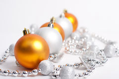 Christmas Decorations. Yellow balls and silver beads on a white Stock Photos