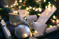 Christmas Decorations. ~ silver balls, ribbons and crackers, with fairy light background Stock Images