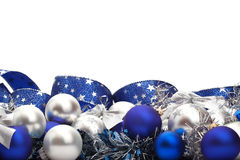 Christmas decorations. Silver and blue Christmas decorations and tree adornments on white background with copy space above Royalty Free Stock Images