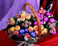 Christmas decorations. Decorative apples small purple balls and toy birdy on the wicker basket Stock Photos