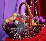 Christmas decorations. Decorative apples small purple balls and toy birdy on the wicker basket Royalty Free Stock Photography