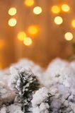Christmas decorations on a background of yellow lights. Christmas decorations. Christmas-tree branch under snow on a background of yellow lights. Vertical frame Royalty Free Stock Images