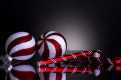 Christmas decorations balls and candy cane. Christmas decorations 2 candy canes and 2 balls red and white shot front on on a grey background with reflection royalty free illustration