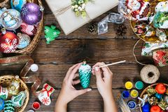 Christmas decorations, balls, toy and gift boxes on old wooden board. Female hands draw New Year decorations. Beautiful frame with free space. Idea for Stock Photos