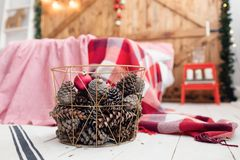 Christmas decorations in basket and pine cones on floor close up. Bedroom is decorated before xmas Royalty Free Stock Photo