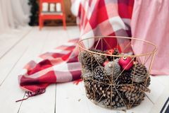 Christmas decorations in basket and pine cones on floor close up. Bedroom is decorated before xmas Royalty Free Stock Image