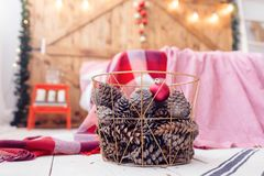 Christmas decorations in basket and pine cones on floor close up. Bedroom is decorated before xmas Stock Image