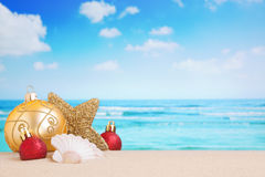 Christmas decorations on the beach, ocean in the back. Christmas decorations and baubles in the sand on a beach on a bright and sunny day royalty free stock images