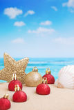 Christmas decorations on the beach, ocean in the back. Christmas decorations and baubles in the sand on a beach on a bright and sunny day stock image