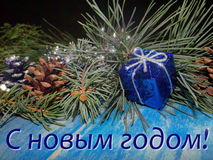 "Christmas decorations. Beautiful Christmas decoration with fir tree branches are on blue wooden boards and the inscription ""happy new year Royalty Free Stock Photography"