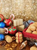 Christmas decorations, biscuits, sweets and wrapped present boxes on a wooden background. Stock Photos