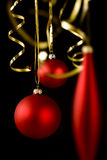 Christmas decorations on black. Red christmas balls and golden ribbons on black background Stock Photography