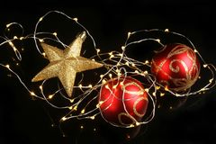 Christmas decorations on black. Christmas decorations, glitter star and baubles with fairy lights on a black background stock photo