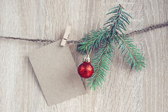 Christmas decorations with a blank card hanging over wooden back Stock Photography