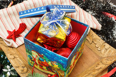 Christmas decorations in the box and gift box on top Royalty Free Stock Photography