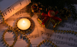 Christmas decorations, burning candle and sheet music. In the dark royalty free stock images