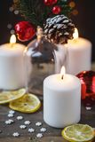 Christmas decorations, burning candles, candy ,citrus, spruce on a wooden background. New Year`s concept. Postcard stock images