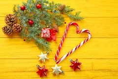 Christmas decorations and candies. On yellow wooden background Stock Photos