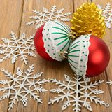 Christmas decorations and candle in on a wooden surface. Christmas decorations, candle in the form of cones and snowflakes on a wooden surface Stock Photo