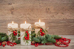 Christmas decorations candles with fir. Christmas decorations: three burning candles, fir, mountain ash, hazelnut. Wooden background Stock Photo