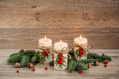Christmas decorations candles with fir. Christmas decorations: three burning candles, fir, mountain ash, hazelnut. Wooden background Stock Images