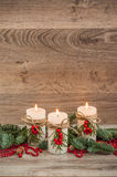 Christmas decorations candles with fir. Christmas decorations: three burning candles, fir, mountain ash, hazelnut. Wooden background Royalty Free Stock Photo